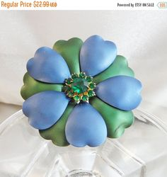 This #vintage flower brooch is just so gorgeous!  It features a large shiny flower blossom in blue and green with a satin finish.  The center is a cluster of prong set green... #ecochic #etsy #jewelry #jewellery #holiday2014etfs