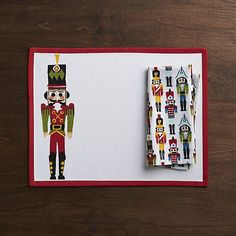 Dressed in holiday regalia, a single nutcracker stands at attention, offset on a white cotton placemat with red border. Sets a festive table with matching napkins and plates.