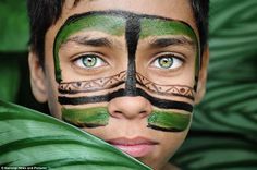 A young member of the indigenous Dessana tribe gazes at the camera with piercing green eyes, while sporting streaks of green and black paint on his face.