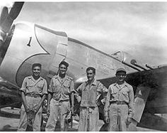 A pilot standing in front of his P-47D with a maintenance crew after a combat mission during World War 2.