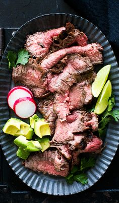 Grilled Carne Asada! Thinly sliced, grilled beef made with marinated, grilled skirt steak or flank steak. Serve with warm tortillas, avocados, and pico de gallo fresh tomato salsa. On SimplyRecipes.com