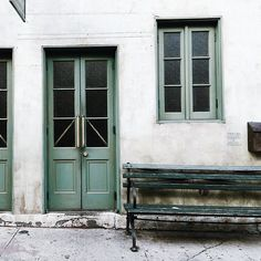 rustic white wall + muted green door with concrete sidewalk in front