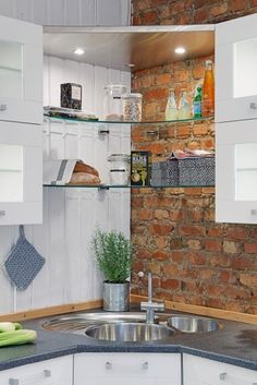 kitchen corner sink + exposed shelves with lights against brick