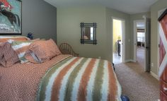This bedroom with an ensuite bathroom from Lennar Minnesota features a fabulous orange and khaki bedspread