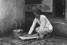 Indonesische vrouw (baboe?) bezig met een wasbord bij een kraan. 1947/01/01. Indonesië, Nederlands-Indië