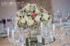 Centro de mesa en tono blanco con toques de rosa en base de espejo.