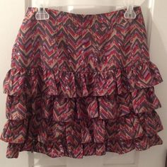 NWOT Banana Republic Ruffle Skirt Taupe, Charcoal, Lavender, Burgandy and maroon. One zipper on the side looks like silk but 100% Polyester. Great even fit all around, very flowy & flattering and still  just long enough for the office. NWOT, never worn. Size 4 but could still fit a 6. Banana Republic Skirts