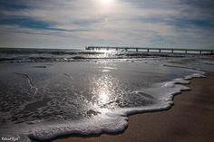 L'écume d'une vague sur le sable vierge