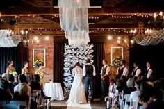 Sheer fabric panels and fairy lights draw the eye from the bride and groom, to the paper cranes backdrop, and finally to the beautiful woode...