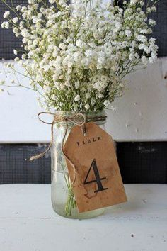 tea stained, vintage-inspired tag table number wrapped around baby's breath centerpiece @myweddingdotcom (mason jars centerpieces)