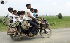 One motorcycle carrying 6 children to school -- India.
