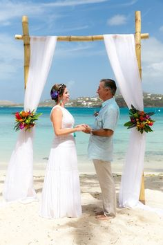 Beach wedding ceremony decor idea - white fabric arch with bright, tropical flowers {Crown Images photography by Sage}