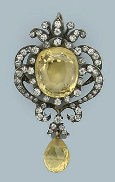AN ANTIQUE SAPPHIRE AND DIAMOND PENDANT   Set with a large cushion-shaped yellow sapphire within a diamond set foliate frame, supporting a later yellow briolette sapphire, late 19th Century