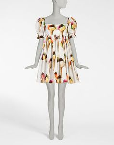 <i>The Spring-Summer 2017 is a journey towards an imaginary Italian Tropic, where the icons traditionally associated with Italy, like bread, pasta and good luck charms are merged with a holiday atmosphere, punctuated by cocktails, ice cream and sequins.</i><br><br>Cotton poplin dress with ice cream print:<br>• Square neck at the front and back<br>• Short puff sleeves with gathered hems<br>• Full high-waisted skirt<br>• Smocked bodice at the...