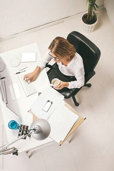 Stock photo of Aerial view of mature business woman working at office.