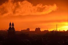 A blood-red sunset over Rotterdam, seen from one of the Lijnbaan apartment buildings. Prominent left in the picture are the two towers of Paradise Church on Nieuwe Binnenweg. On the horizon we see a forest of chimneys and harbor cranes. In between are the roofs of the Old West neighbourhood and the semi-highrise buildings around Coolhaven.