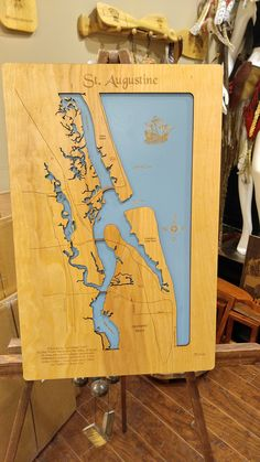 """St Augustine, Florida: Standout Wood Map Wall Hanging. This is a beautifully detailed, laser engraved and precision cut topographical map of St. Augustine, Florida with the following interesting stats carved into it: Founded in September 1565 by Don Pedro Menendez de Aviles of Spain, St. Augustine is the longest continually inhabited European-founded city in the United States - more commonly called the """"Nation's Oldest City."""" This stand out map is mounted onto a tranquil blue background…"""