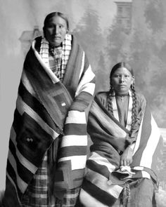 Two Strikes daughters, Lakota Sioux women, Pine Ridge Agency, South Dakota, in front of a painted backdrop. Photograph: 1891.