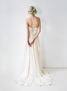 This gown features a sweetheart neckline and low back. The skirt is made of 10 yards of hand-draped chiffon, which catches movement and the wind whimsically. The bodice is made of a stunning chorded French lace which is slightly darker than the lining, making its design pop. The back dips into a lace-up, which allows for size flexibility and a perfectly adjustable fit.  The bodice is constructed with two sets of interfacing and is fully boned to give structure and support. Many of our brides…