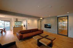 コンクリート・木・鉄でシンプルに構成されたマンションリノベーション。 築23年の杉並区の高級マンションのスケルトンリノベーション事例です。ベースとなったのはコンクリート打ち放しの壁の力強い素材感で、それにマッチする床材(幅広パテ埋めの野性的なフローリング)、塗装の壁と天井(白・青・朱色・緑等)、鉄製の扉とガラス、ダイナミックな横目突板で作った家具等を、バランスを調整しながらシンプルに再構築したインテリアリフォームです。 約70平米(40畳)のLDKには、コンクリートの壁、白色の壁に溶け込む塗装の造作家具そして大型アイランドキッチンをレイアウトし、各壁・コーナー毎に少しずつ違ったシーンが展開するようなインテリアを目指しました。寝室の並べ方や玄関のレイアウトはオーソドックスですが、素材または特徴的な色彩でそれぞれの空間にユニークな性格を与えています。長い廊下には、本棚と書見用のベンチを設け、書斎としての機能を付加しています。 空調を始め、給水給湯・ガスも全て引き直し、外壁周りの断熱材も吹き直し、空間としての性能もベースアップしています。…