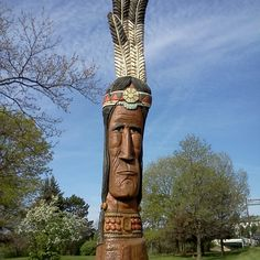 Downtown Cuyahoga Falls, Cuyahoga Falls, Ohio — by Adam Miller. Wood carving next to a park along a river