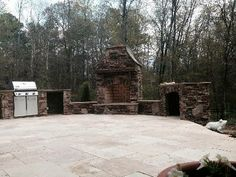 Charlotte outdoor fireplace with outdoor kitchen on Travertine patio