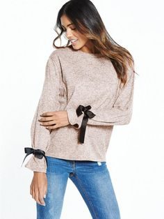V by Very Tie Sleeve Cuff Jersey Knit Top Can we take a moment to appreciate the simple-meets-statement design of this V by Very knitted top? Its jersey marl fabric and loose silhouette is offset with black ribbons to the sleeves, which tie a touch of feminine charm into your look. Styling Ideas Wear yours with denim (A-line mini or skinny jeans?) and ankle boots or trainers for a chic weekend style.