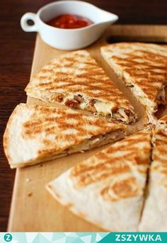 Zobacz zdjęcie składniki: -4 placki tortilli -200 g sera żółtego -125 g kurek -1 udo kurczaka -1 cebula -3 łyżki jogurtu greckiego -½ łyżeczki posiekanej pietruszki -łyżka masła -przyprawa warzywna (typu Vegeta) -sól -pieprz przepis: Kurki dokładnie myjemy, a cebulę drobno siekamy. Ser ścierany na tarce o grubych oczkach. W garnku zagotowujemy wodę, doprawiamy przyprawą warzywną i gotujemy udko z kurczaka (około 20 minut). Gdy będzie ugotowane, odstawiamy do ostygnięcia i oddzielamy mięso…