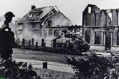 0210352 Coll. Chr. Warnar: Engelse tank rijdt Asten binnen De soldaat links staat op wacht voor de kerk. De verwoeste huizen zijn van Toon van Hoek en de familie Eijsbouts .