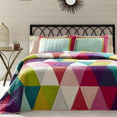 The Taylor Collection is geometric, bold, patterned, trendy and fun! Bright solids colors in bright and medium pink, purple, indigo, light blue-teal, yellow-green-bright green, grey, crème, gossamer pink, and coral are repeated in a rainbow of isosceles triangles.  See this at The BitLoom:  https://www.thebitloom.com/collections/bohemian-eclectic-bedding/products/taylor-pink-purple-blue-green-triangle-quilt-sets