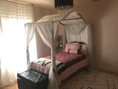 French Boutique little girls room. Pink and white stripe walls. Canopy bed. Chandelier.