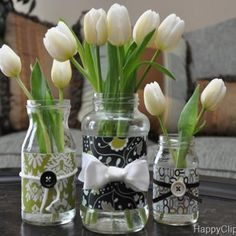 """Keep old pickle jars, iced coffee bottles, etc.  Mismatch styles and sizes to create beautiful centerpieces with coordinating colors.  And we all have a drawer full of those """"extra buttons"""" that come with clothes, right?  Might as well put them to use."""