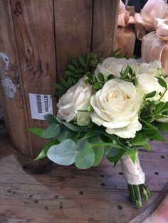 Four seasons roses with eucalyptus bound with ivory ribbon and pearl pins