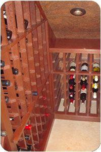 Small wine storage space with quarter round and mahogany wine racks with display rows