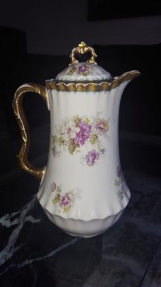 FOR AUCTION IS AN ANTIQUE PORCELAIN COFFEE/TEA/DEMITASSE/CHOCOLATE POT WITH FLOWERS AND HEAVY GOLD DETAIL. IT IS MARKED  AKCD LIMOGES FRANCE . IT MEASURES APPROX 9 INCHES TALL BY APPROX 6 INCHES WIDE.