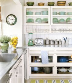 country living kitchen - not so wild about the visible drawers, but do like the open cabinets and the green/blue striped rug and stainless worksurface.