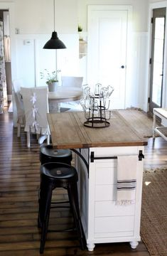 a mini kitchen island in white with a wooden tabletop and rails on each side can be used for breakfasts or having drinks