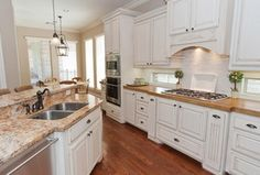 Condo? White cabinets and hardwood floors Traditional Kitchen with Wood counters, Stainless undermount 2-basin sink, Raised panel, Bronze cup pull, Custom hood