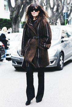Emannuelle Alt wears a brown and black striped blanket coat with a belt, flared jeans, and black boots