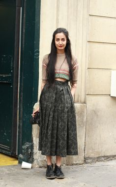 Nadia Sarwar. cropped top, pleated midi skirt and black lace up boots.
