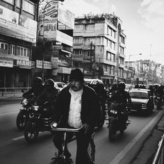 Streets of Kathmandu 6 by Maurits Bos. Man cycling in the middle of the street. Motorcycles and cars. Street photography. Nepal. Kathmandu. Black & White photography.