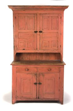 """AMERICAN PAINTED STEPBACK CUPBOARD.  Ca 1840-50, pine. Two-piece cupboard with raised panel construction with square nailed drawers. Large ogee crown molding, inset brass latches and iron butt hinges. Later pink-salmon paint. Very high pie shelf. Top, 49.5""""h. 52""""w. 15.25""""d. Base, 36""""h. 47.5""""w. 21.5""""d."""