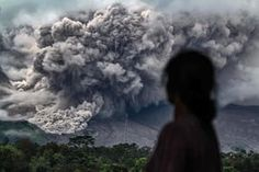 A woman watches an eruption from the Mount Sinabung volcano from the village of Tiga Pancu.
