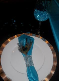 Silver chargers, peacock feathers, turquoise napkins with diamond band napkin ring