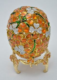 """Lindo objeto decorativo em metal dourado com esmaltes e aplicações em strass representando """"Ovo&"""