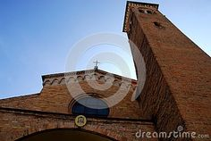 Photo made in the center of Padua in Veneto (Italy). In the picture you see, he shoots from the base, the upper part of the facade and the bell tower, built of brick, the ancient church of St. Nicholas. The simple but beautiful church in shadow is bounded by the blue sky made pale by sunlight.