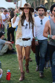 Coachella, el festival favorito de las celebrities. Alessandra Ambrosio con camisola y shorts blancos, sombrero de ala ancha , chaleco y botas de cowboy con tachuelas. Un look muy hippie perfecto para la ocasión.