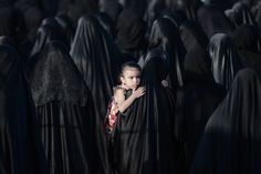 A Bahraini girl is carried by her mother during the funeral of Sayed Omran Sayed Hameed, on May 28, 2013, in the village of Karzakkan, south of Manama. Hameed, 26, died at hospital after developing respiratory complications and his relatives claim that his death is due to the inhalation of poisonous tear gas that riot police used during a protest in May 2013. (Photo by Mohammed Al-Shaikh/AFP Photo)