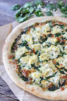Spinach Artichoke Pesto Pizza Recipe on twopeasandtheirpod.com My all-time favorite pizza! #pizza #vegetarian
