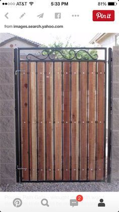Scrolled wrought iron driveway gate with write perforated metal .